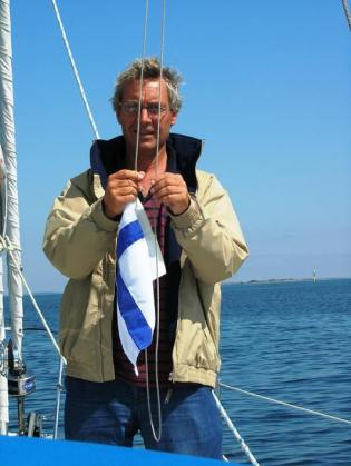 The skipper raises the Finnish courtesy flag